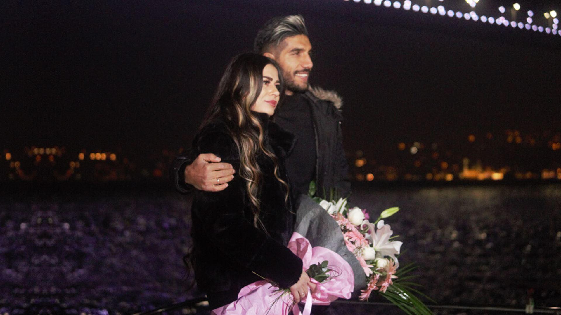 İstanbul gecesinde, denizde gezinti yapan Deryat ve Boğaz Köprüsü manzarasında mutlu bir çift