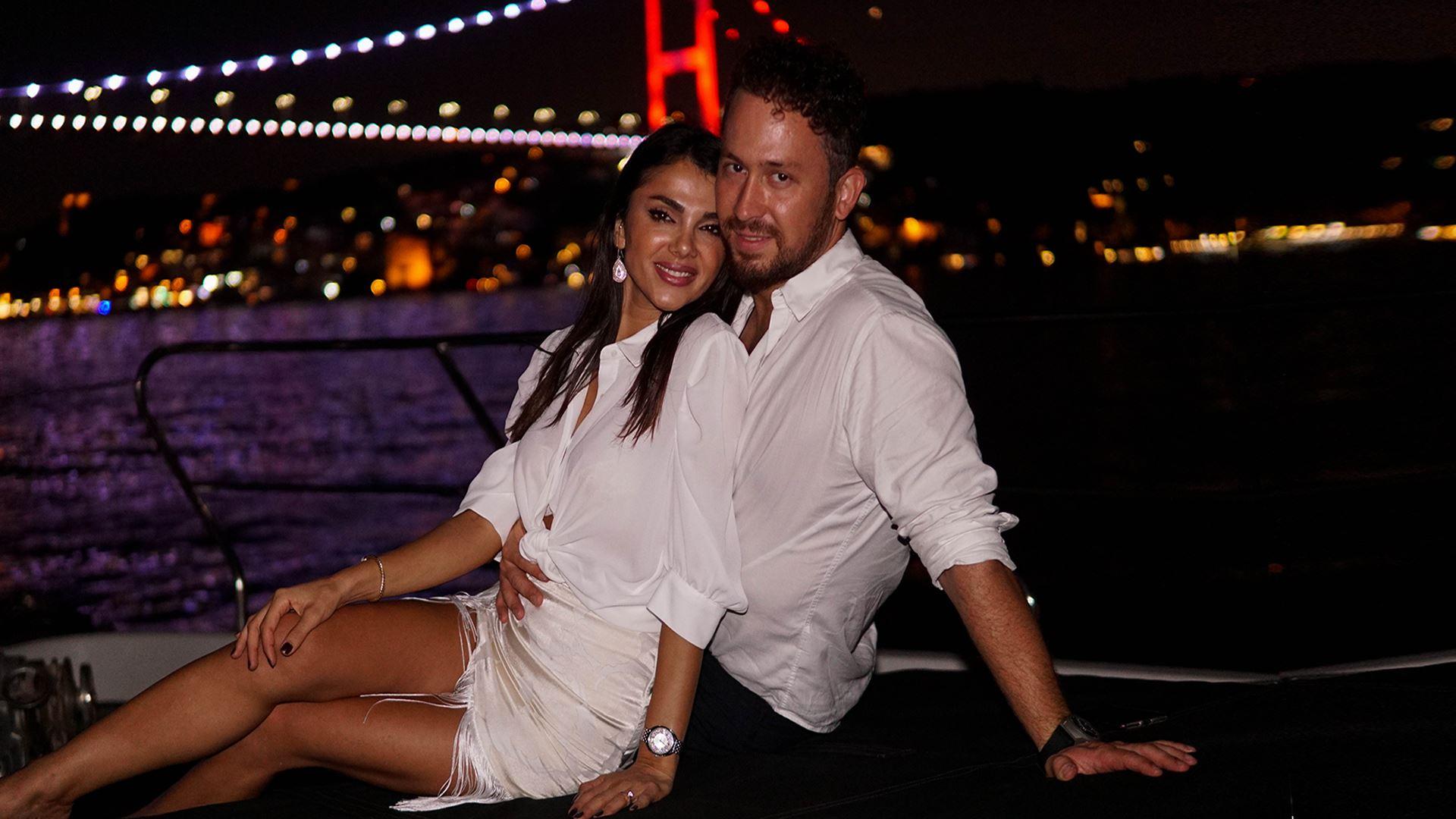 İstanbul'da gün batımında, denizde gezinti yapan Deryat üzerinde mutlu bir çift sarılarak poz veriyor