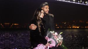 İstanbul gecesinde, denizde gezinti yapan Deryat üzerinde Boğaz Köprüsü manzarasında mutlu bir çift